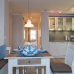 Esstisch und moderne offene Küche mit nagelneuen Einbaugeräten - So macht Kochen Freude.
